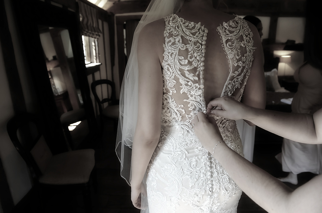 Atmospheric wedding photo of the back of the Bride's beautiful wedding dress being fastened by a bridesmaid in Surrey at the bijou Cain Manor in the Bridal Suite