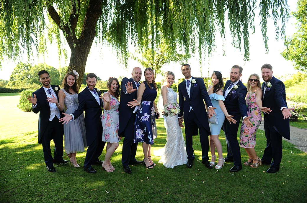 Fun group wedding photo taken on the lawn at the lovely Surrey wedding venue Cain Manor of couples waving their 'Jazz hands'