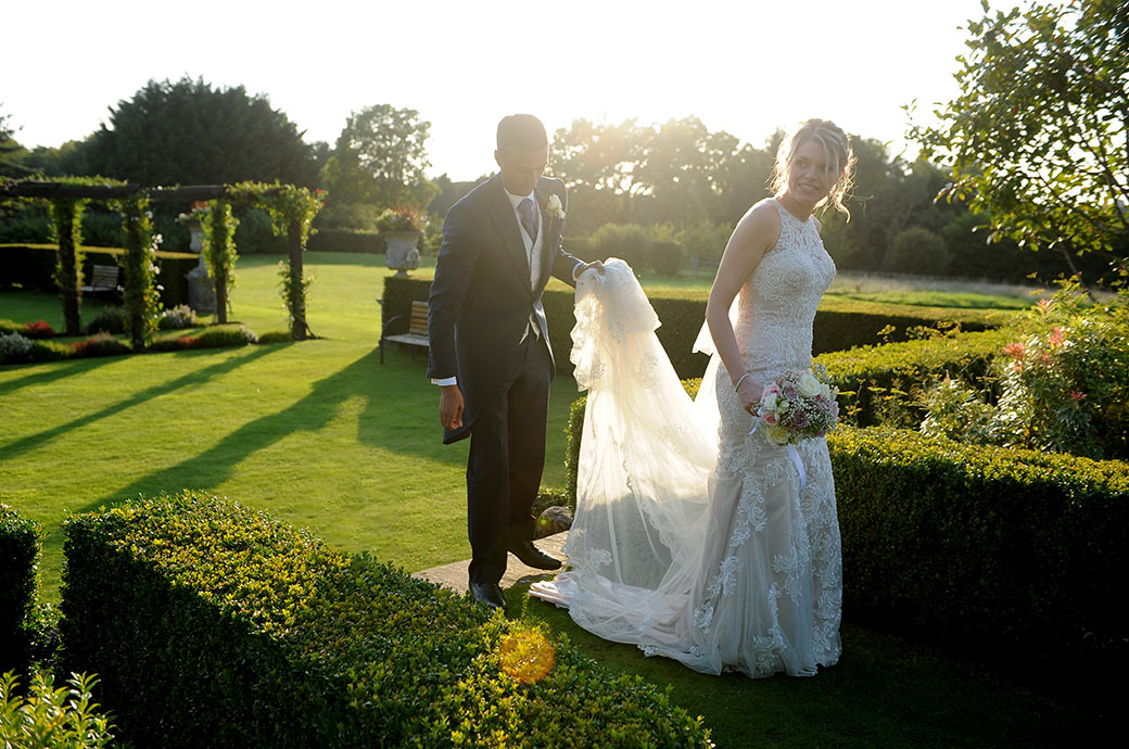 Gallant Groom helps his Bride with her dress at the wonderfully homely and picturesque Cain Manor in Surrey as they cross the lawn in the bright sunshine