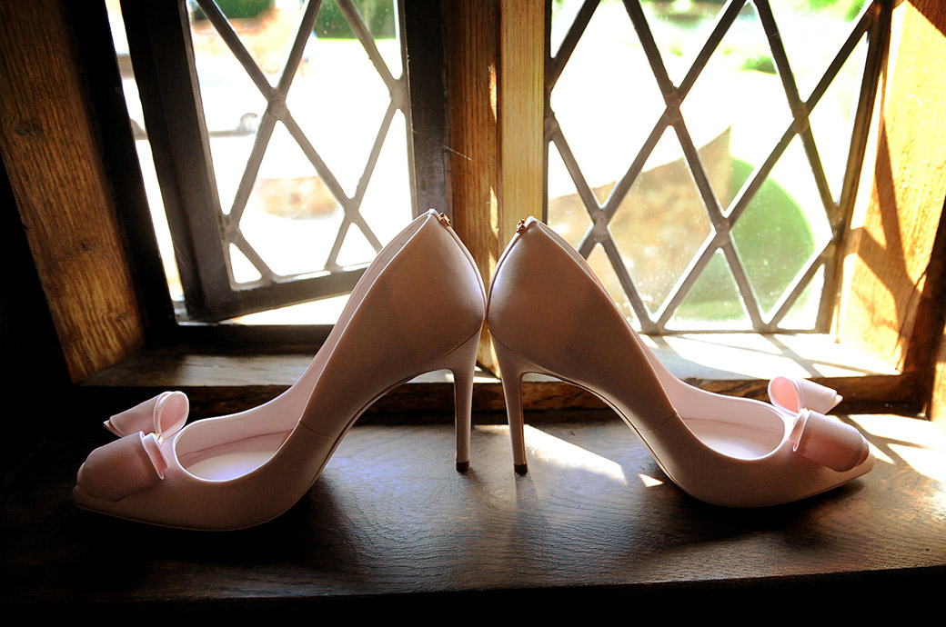 Elegant pink wedding shoes with  a pink bow captured in this picture taken in the window sill of the Cain Manor Bridal Suite in Headley Down Surrey