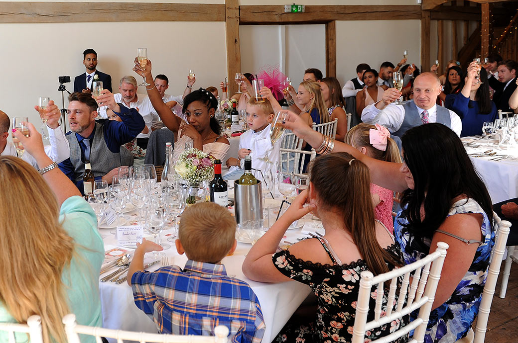 Wedding guests at the lovely Surrey wedding venue Cain Manor raise their glasses to toast the newlywed couple at the end of the speeches held in the Music room