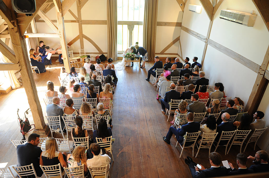Wedding picture from the minstrel gallery of the Music Room at Cain Manor Surrey taken as the couple sign the marriage register whilst a string quartet play