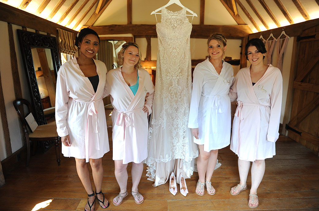Smiling Bride and Bridesmaids standing by the hanging wedding dress in their dressing gowns and sandals captured in the Bridal Suite in Surrey at the Cain Manor wedding venue