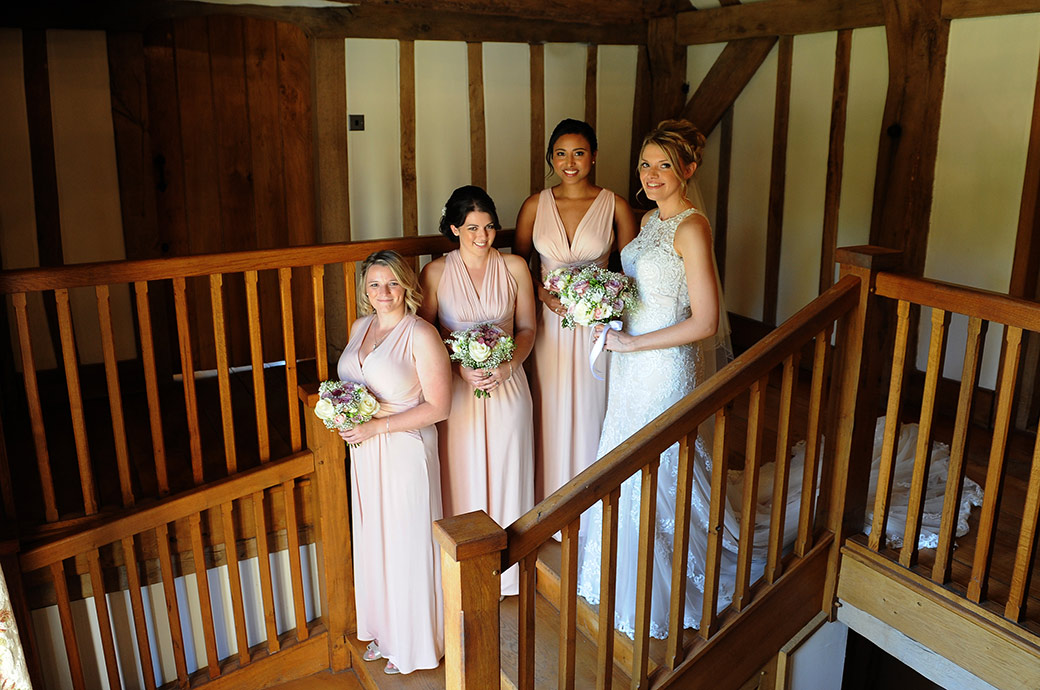 A final wedding photo of the Bride with her Bridesmaids at Cain Manor in Surrey on the staircase just before leaving for the marriage ceremony in the Music Room