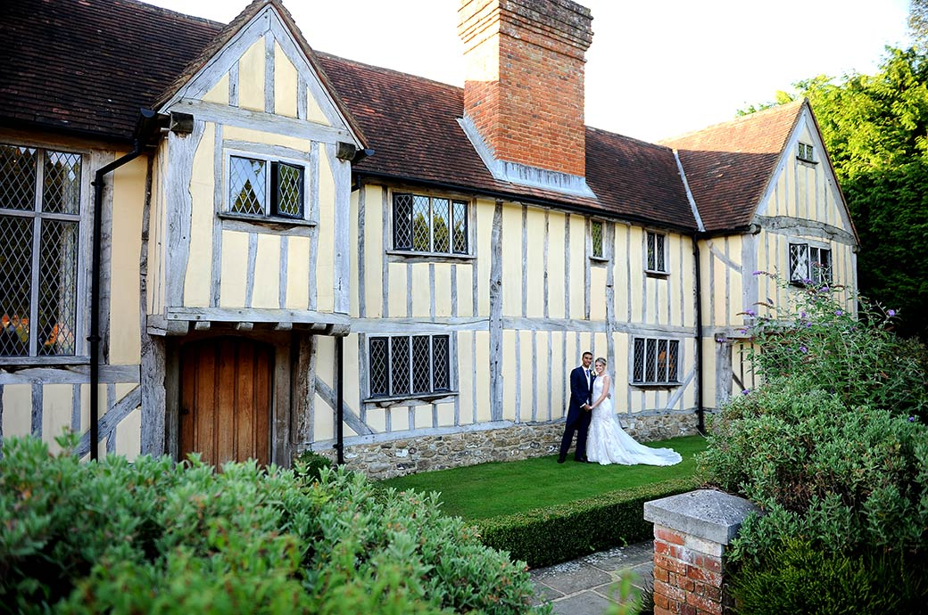 Lovely wedding photograph of a Bride and Groom standing before the chocolate box looking Cain Manor wedding venue in Headley Down Surrey