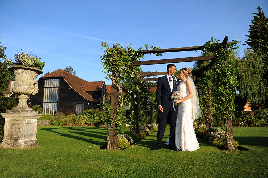 Romantic wedding picture from Surrey wedding venue Cain Manor of the Bride and Groom standing at the end of the rose arbour looking into each others eyes