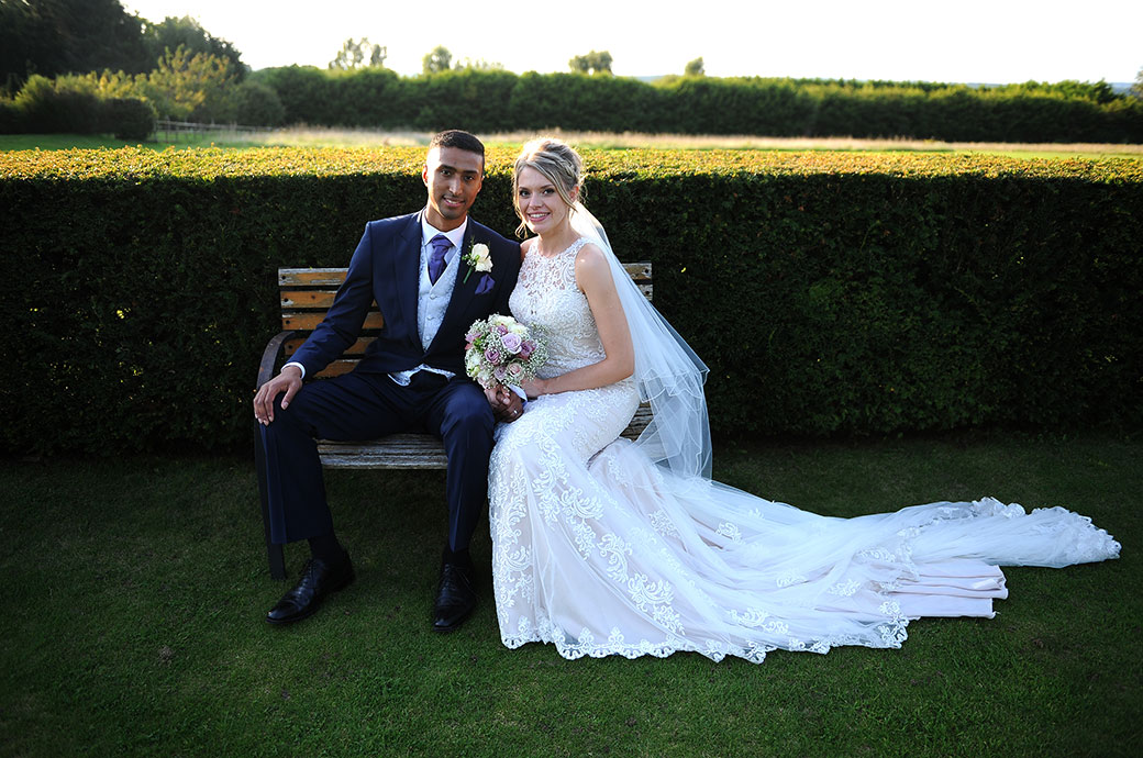 Fresh and relaxed looking newlywed couple pictured at Surrey wedding venue Cain Manor sitting on a garden bench on a lovely summer's evening