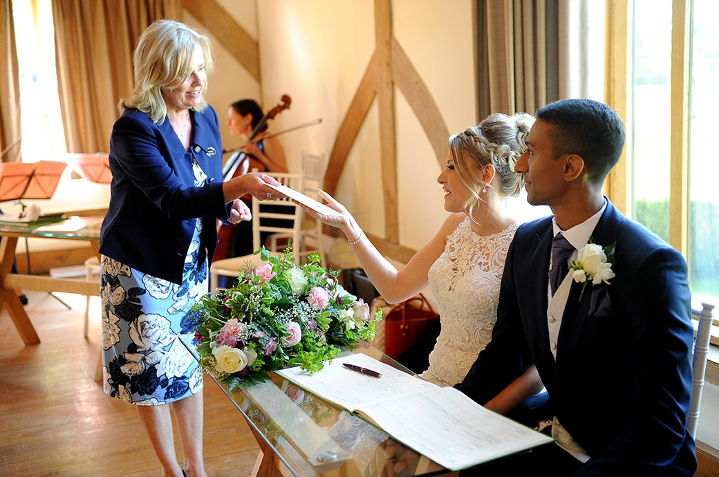 The Registrar hands over the marriage certificate to a smiling Bride in the lovely Music Room at the popular and homely bijou Surrey wedding venue Cain Manor
