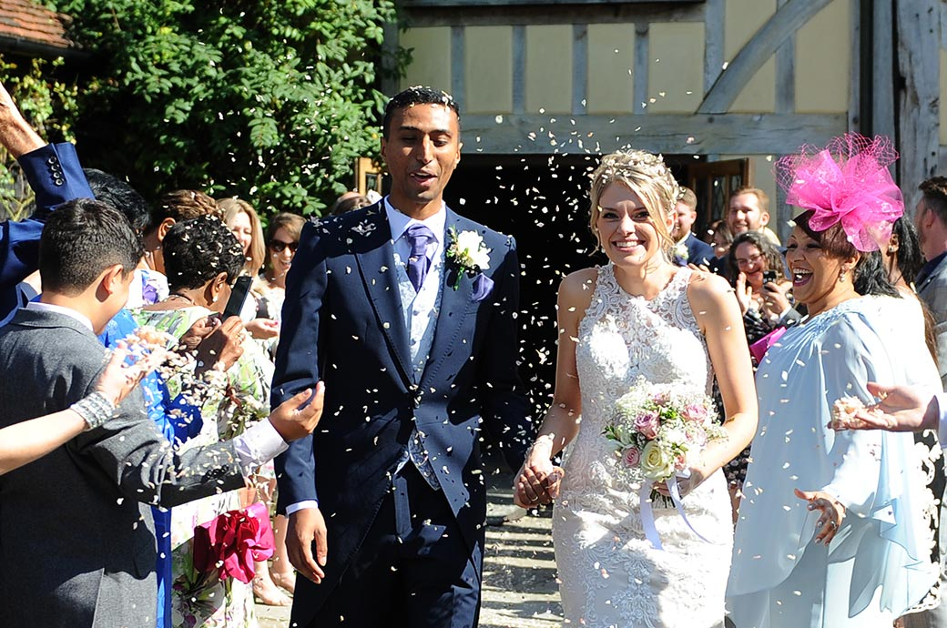 Smiling Bride walks with her husband through a confetti shower out on the patio at Cain Manor a wonderful homely and popular wedding venue in Headley Down Surrey