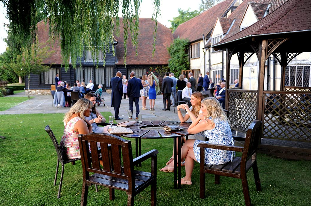 Wedding guests relaxing and chatting out on the patio and lawn during the evening reception at the picturesque and homely Cain Manor wedding venue in Surrey