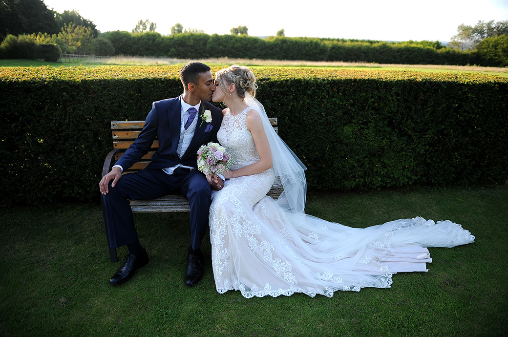 Romance in the grounds of the picturesque Surrey wedding venue Cain Manor as the newlywed couple take time out and sit on a garden seat and kiss