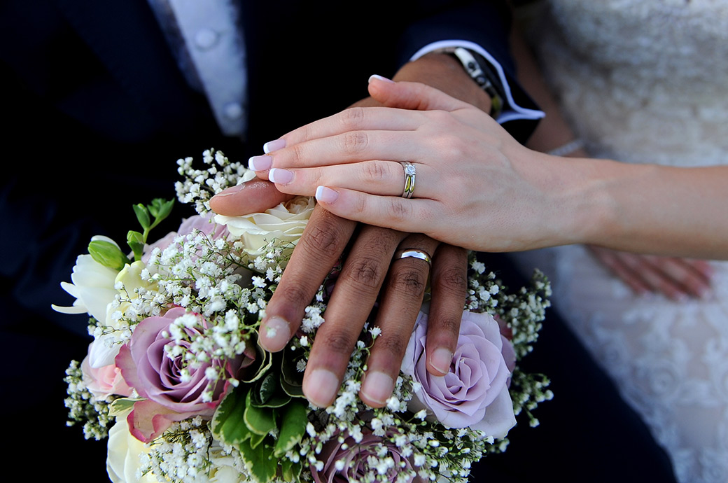 Picture of the Bride and groom's wedding rings taken at the  popular wedding venue Cain Manor in Headley Down Surrey as they rest their hands on the bride's bouquet
