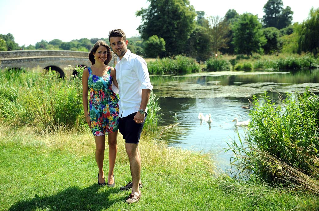 Delightful pre wedding picture shot on the banks of a river with Five Arches Bridge in the background in Foots Cray Meadows, Sidcup Kent