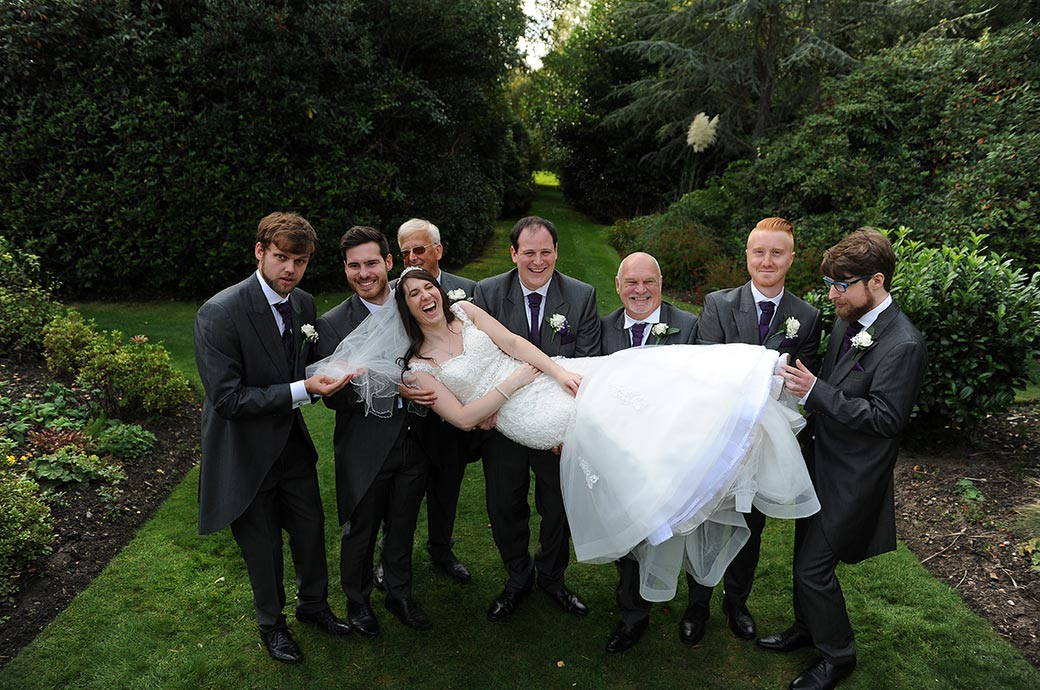 Groom and groomsmen pictured at the lovely homely Surrey Wedding venue Gorse Hill get the Bride laughing as they lift her up on the lawn