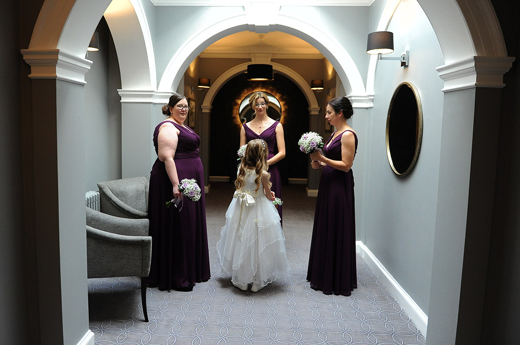 Flower girl and bridesmaids at the homely and popular Surrey wedding venue Gorse Hill captured waiting for the Bride out on the landing outside the bridal suite