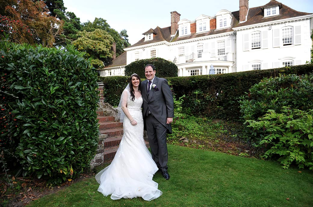 Smiling Bride and groom standing before the steps at Surrey wedding venue Gorse Hill after a romantic walk through the tranquil green gardens
