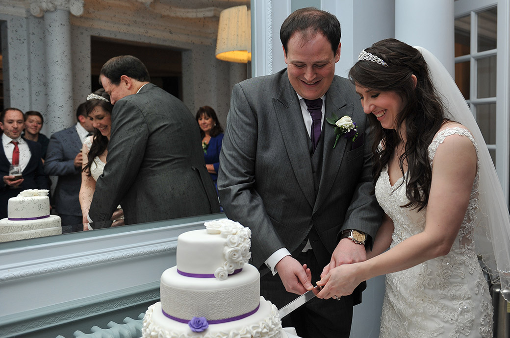 Smiling Bride and groom enjoy cutting their wedding cake captured at relaxed and homely Surrey wedding venue Gorse Hill in The Lounge reception room