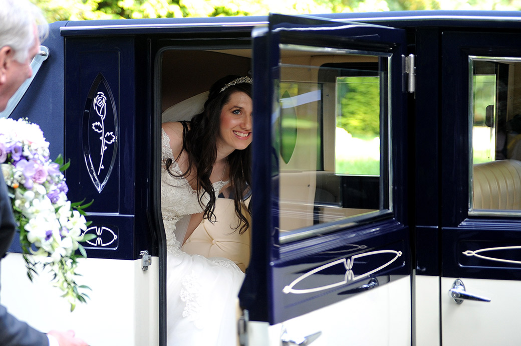 A picture of pure excitement as the lovely Bride emerges smiling  from her bridal car after leaving Surrey wedding venue Gorse Hill Woking for her church marriage ceremony