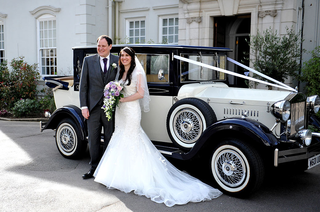 Smiling Bride and groom standing in front of their classic wedding car at the arrival at the welcoming Surrey wedding venue Gorse Hill for their reception