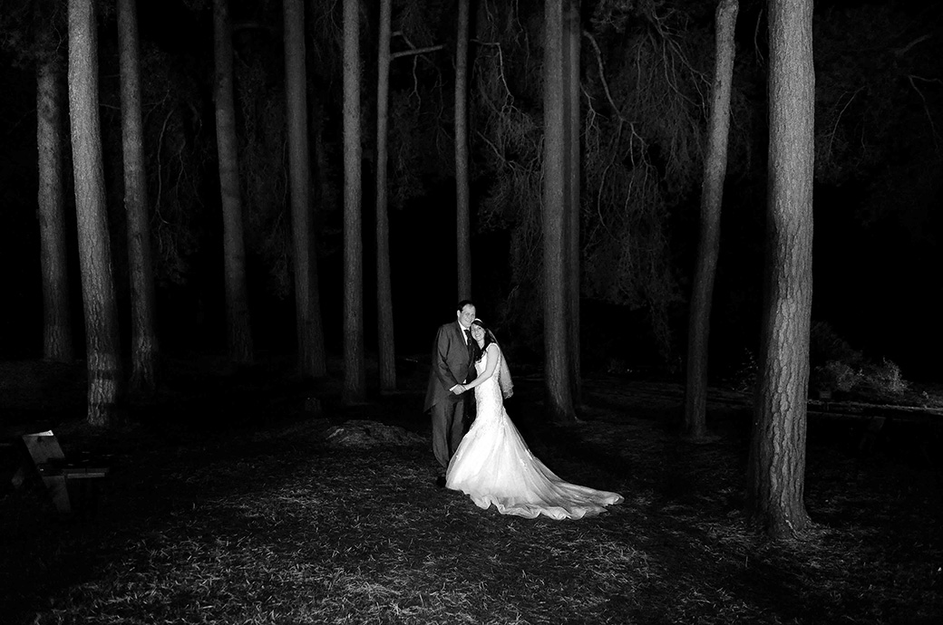 Happy smiling Bride and groom pose for a romantic night time wedding picture beneath the trees at the ever lovely Gorse Hill wedding venue in Surrey