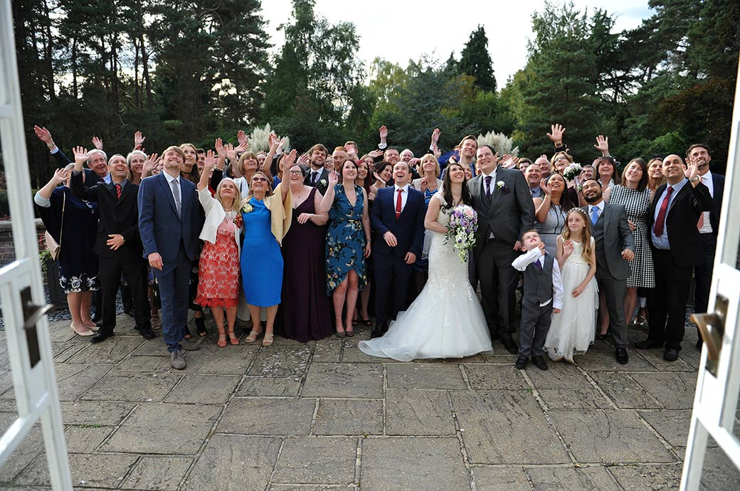 Wedding picture taken from The Lounge at the lovely Gorse Hill venue in Surrey of everyone waving up at the photographer on the Bridal Suite balcony
