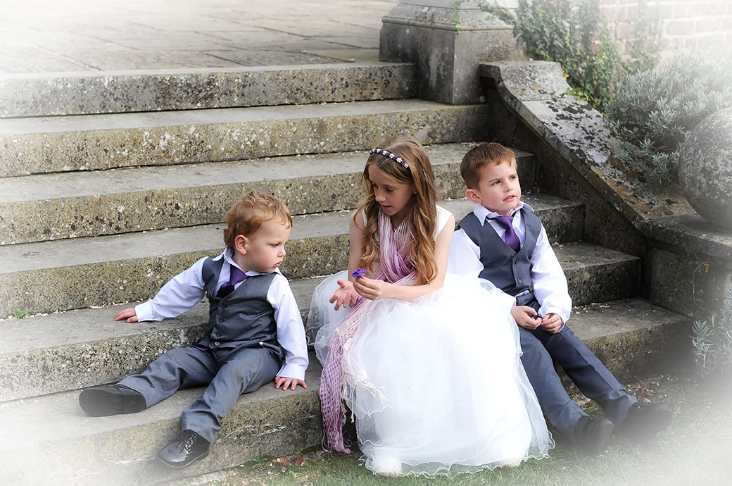 Wedding photograph of cute page boys and a flower girl playing on the garden steps at the relaxed and welcoming Surrey wedding venue Gorse Hill in Woking
