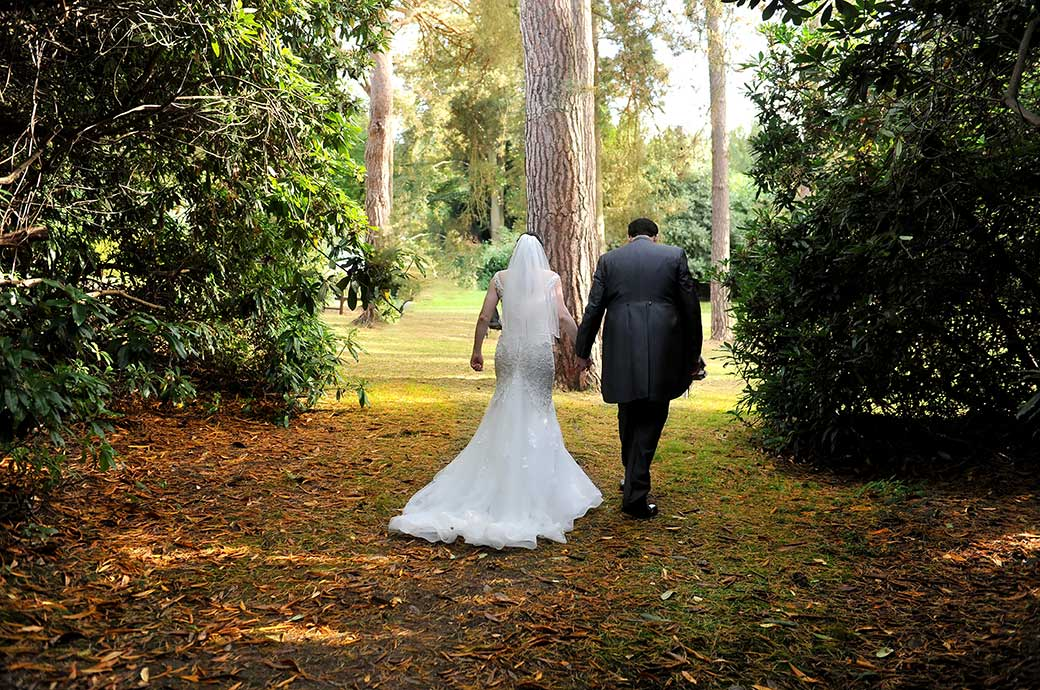 Bride and groom walk hand in hand along a path through the Rhododendron bushes at Gorse Hill a popular Surrey wedding venue in Woking