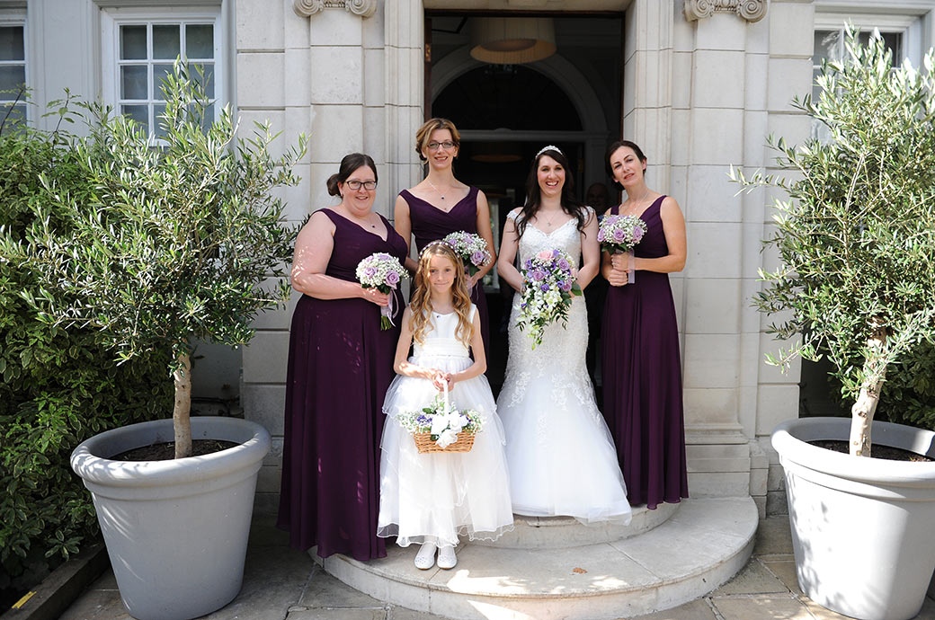 Bride poses with her bridesmaids and flower girl on the front steps of the popular Surrey venue Gorse Hill Woking prior to leaving for her traditional church wedding