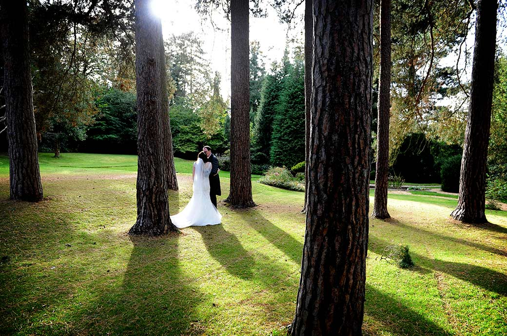 Newlyweds at the popular and homely Surrey wedding venue Gorse Hill have a discrete and romantic kiss amongst the tall trees