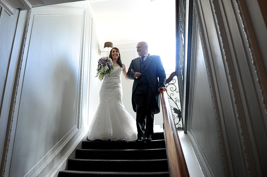 Proud Father takes his smiling Bride on his arm down the stairs of the homely wedding venue Gorse Hill in Surrey on route for a church marriage ceremony