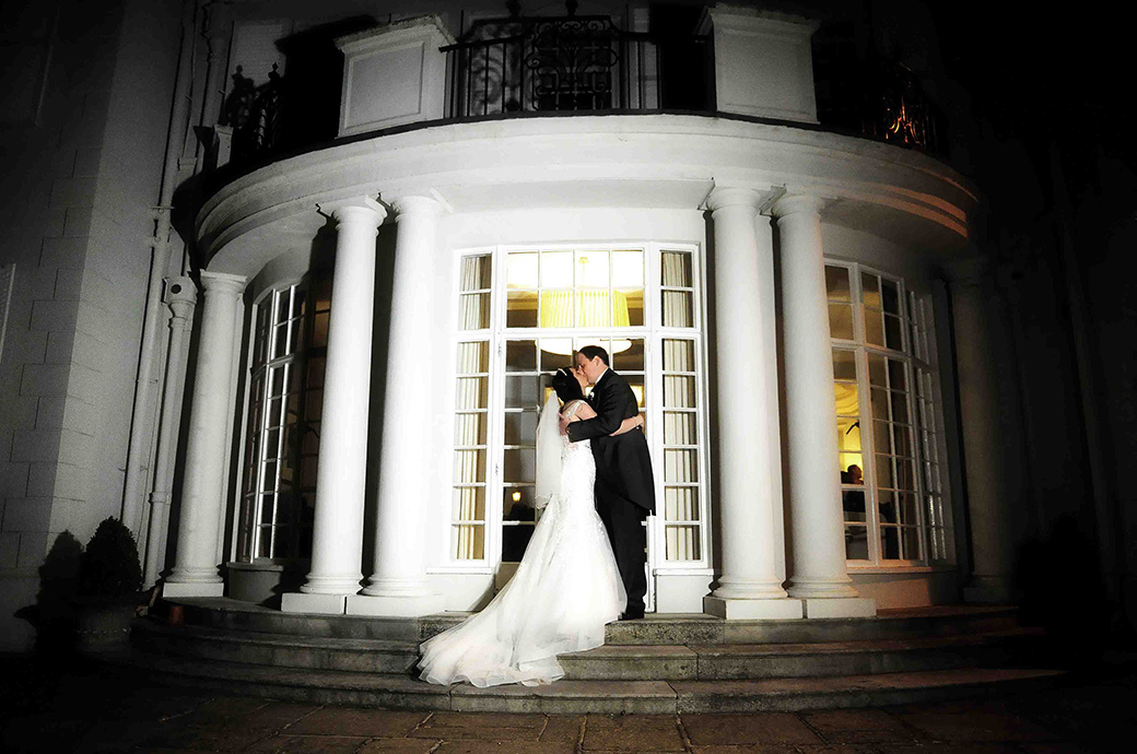 Romantic newlyweds kiss outside the doors to The Lounge captured at night time at the welcoming and relaxed Surrey wedding venue Gorse Hill
