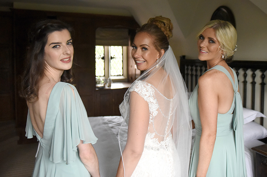 Happy Bride smiling along with her Bridesmaids as they get ready to leave the Nursery Suite for the marriage ceremony in The Orangery at Great Fosters wedding venue in Egham Surrey