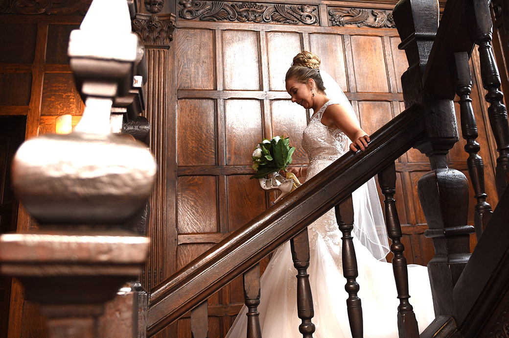 Bride watches her step as she descends the staircase from the Nursery Suite on route to The Orangery captures at the amazing Surrey wedding venue in Egham Great Fosters