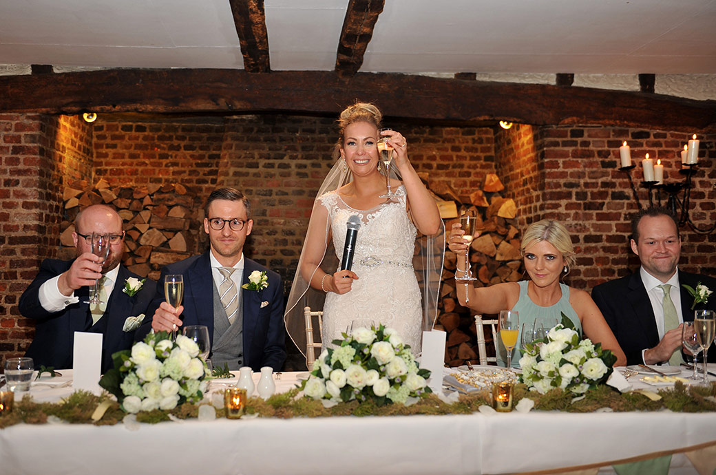 A happy Bride raises her champagne in a top table toast after her wedding speech at Surrey hotel and event venue Great Fosters in the wonderfully old Tithe Barn