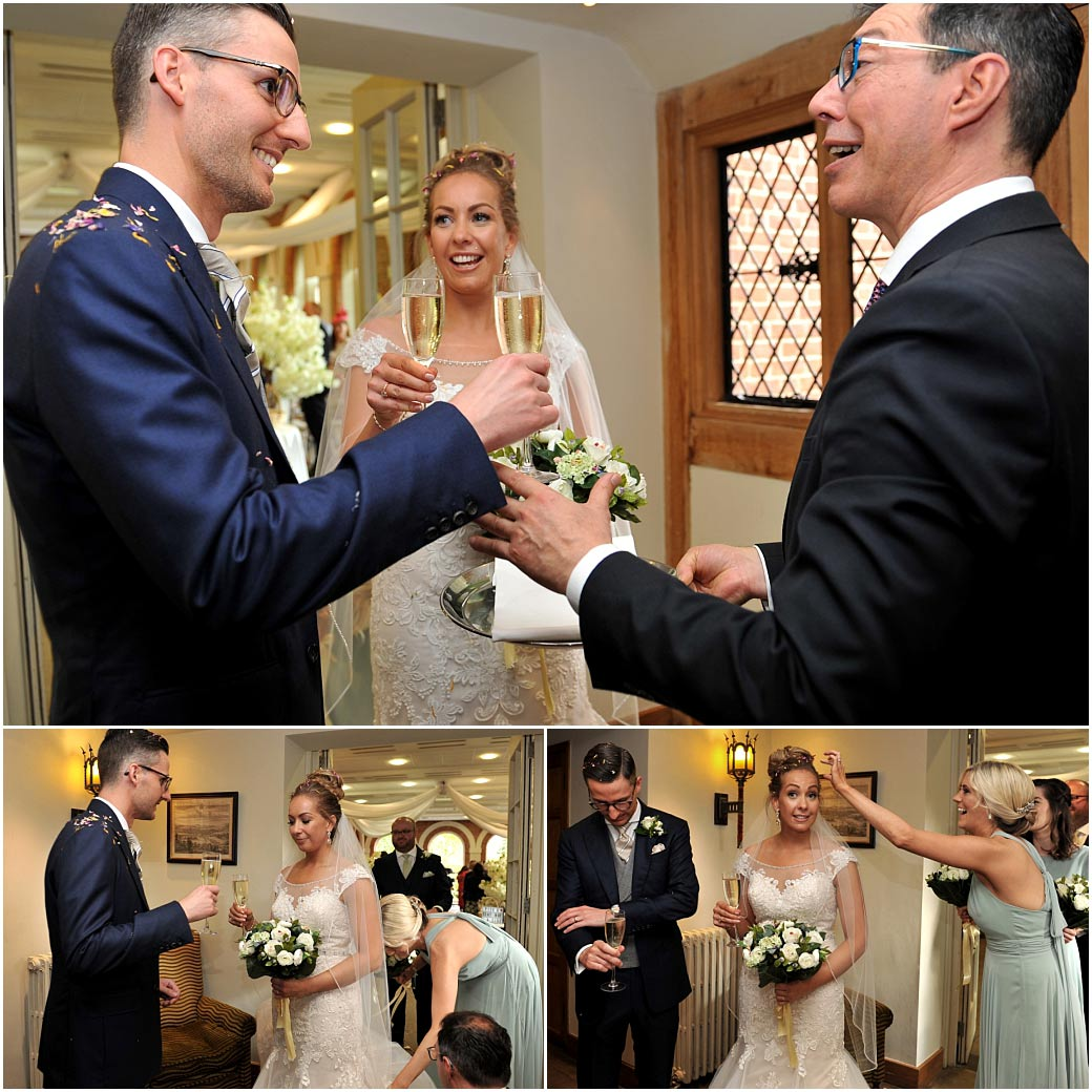 Bride and Groom at Surrey wedding venue Great Fosters celebrate with champagne after braving the confetti shower thrown down the aisle of The Orangery