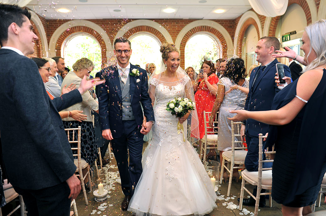 Smiles and laughter at the wonderful Surrey venue Great Fosters as the Bride and groom walk down The Orangery wedding aisle full of flying confetti
