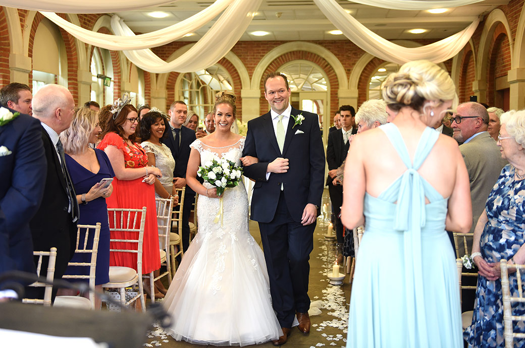 All smiles as a Bride walks down the wedding aisle on the arm of a friend captured in The Orangery at the fabulous Great Fosters venue in Surrey