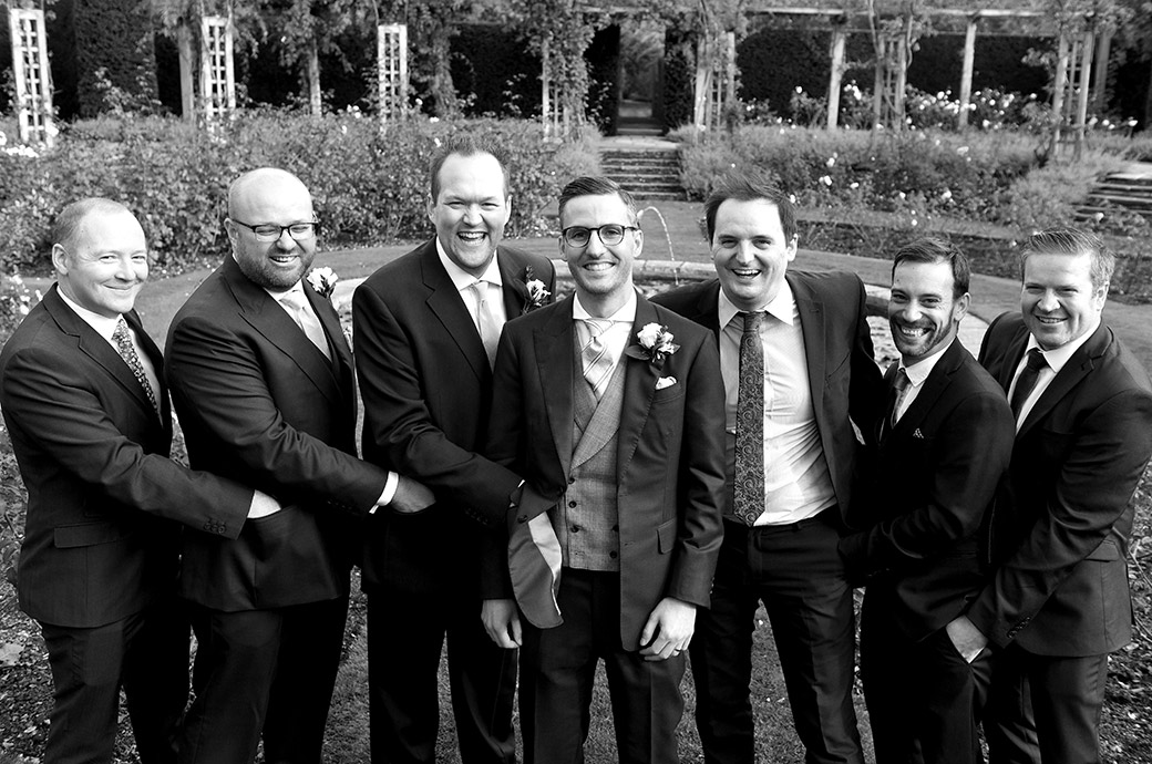 Gents have fun with the Groom as they place their hands in each other's pockets taken in the rose garden at the ever popular wedding venue Great Fosters in Egham Surrey
