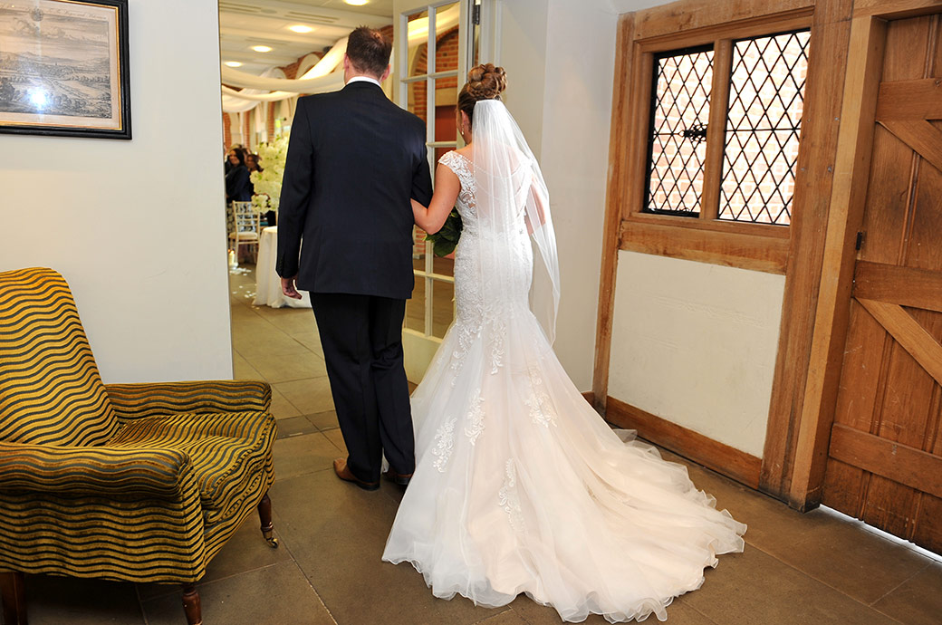 View from behind of a Bride on the arm of a friend at Surrey wedding venue Great Fosters taken as they are about to enter The Orangery to walk down the aisle