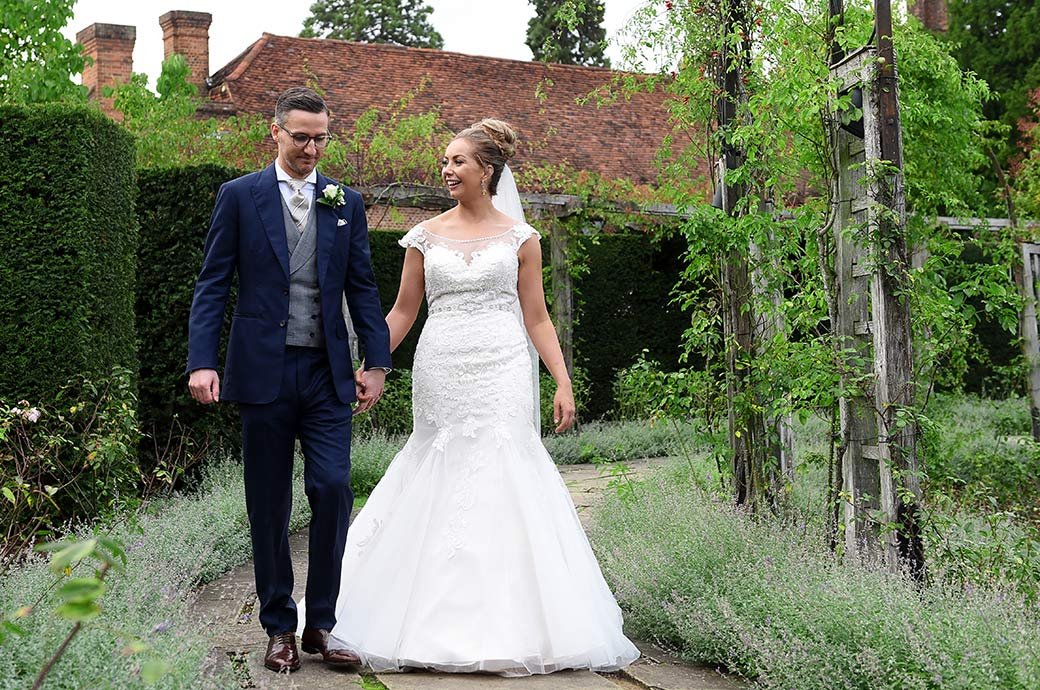Happiness captured as a lovely bride chats to her handsome groom as they walk through the beautiful and tranquil sunken rose garden at Great Fosters in Egham Surrey