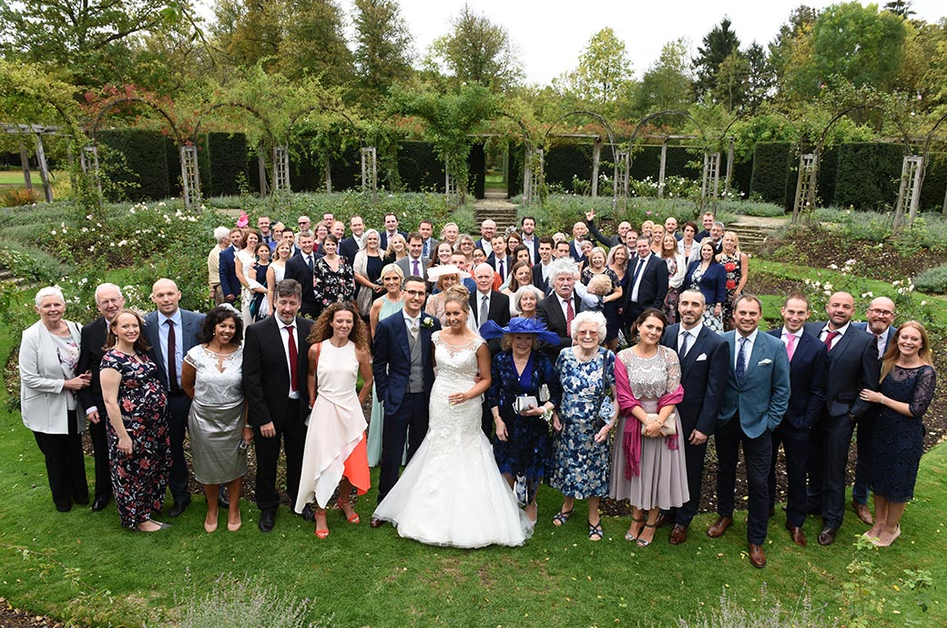 The classic everyone at the wedding picture taken in the beautiful circular rose garden at the historic Great Fosters hotel venue situated in Egham Surrey