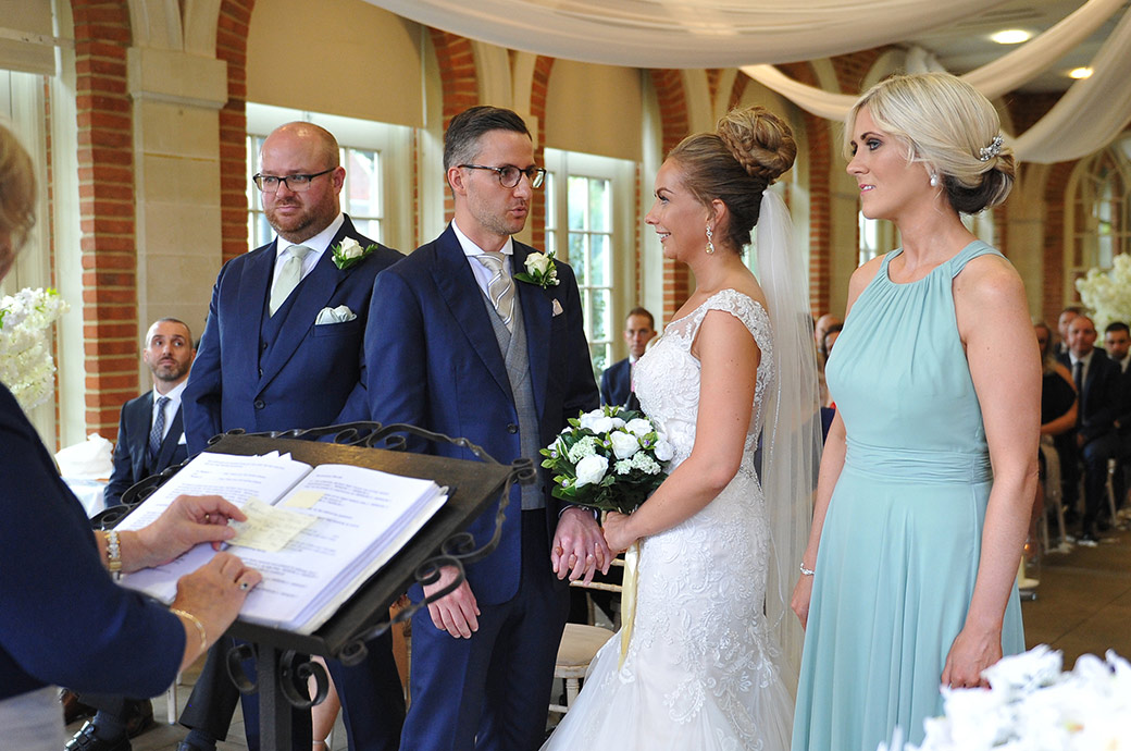 Excited Bride listens as the Groom says his wedding vows in the light and airy Orangery at the fabulous Surrey wedding venue Great Fosters in Egham village