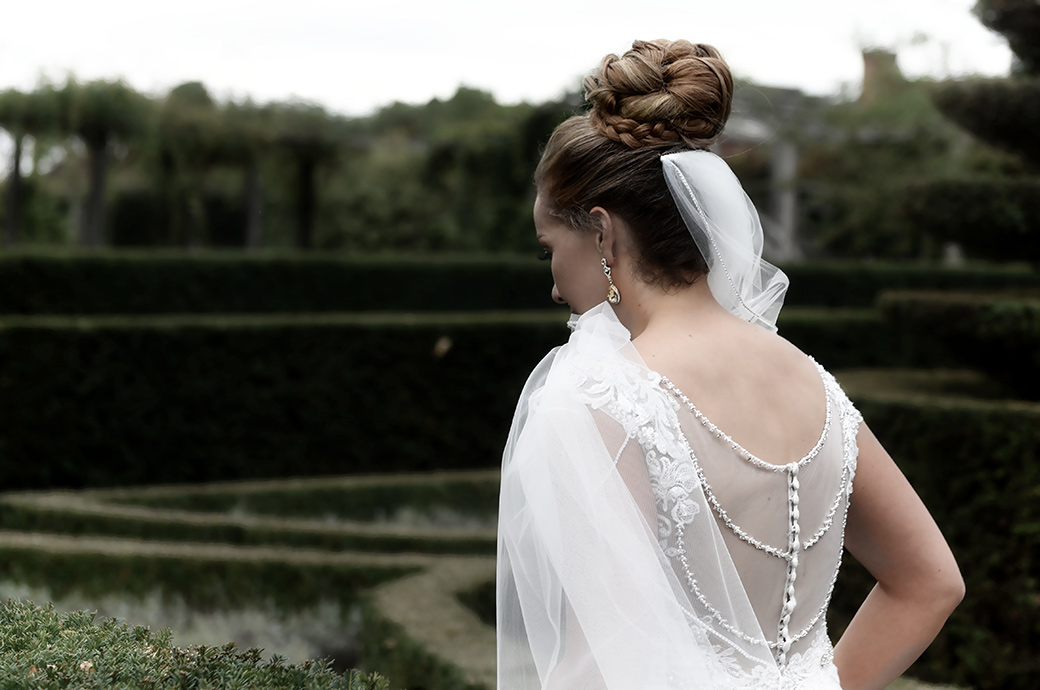 Fine details of the Bride's hair, ear rings and back of wedding dress captured at the stunning Surrey venue Great Fosters in the genteel formal Parterre garden