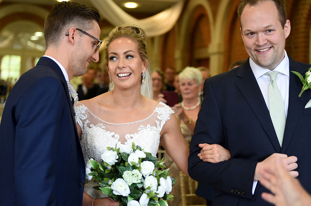 An emotional smiling Bride captured at stunning Surrey wedding venue Great Fosters looks into the eyes of her Groom as she reaches the end of the aisle of The Orangery