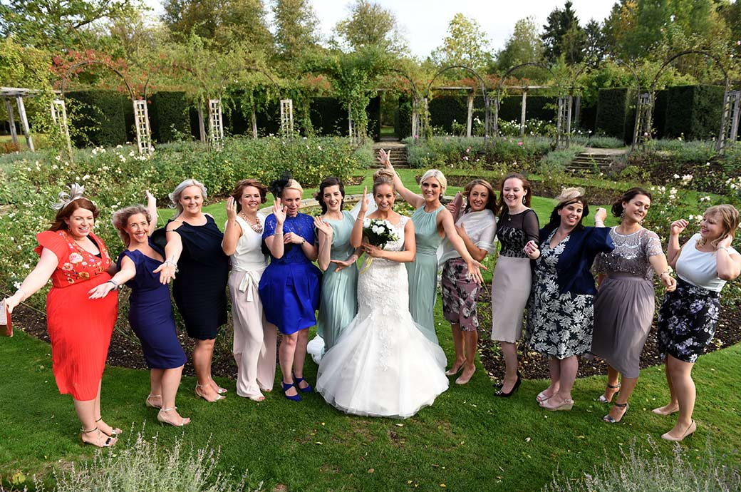 Bride and ladies at Surrey wedding venue Great Fosters have fun as they show off some of their hen night dance moves as they stand in the beautiful rose garden