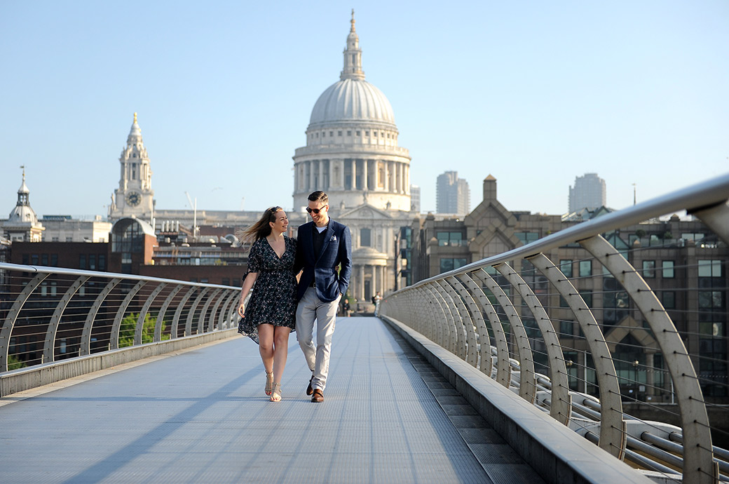 Relaxed couple captured during their pre wed shoot as they leisurely stroll along the Millennium Bridge from St Paul's to Tate Modern by Surrey Lane wedding photographers
