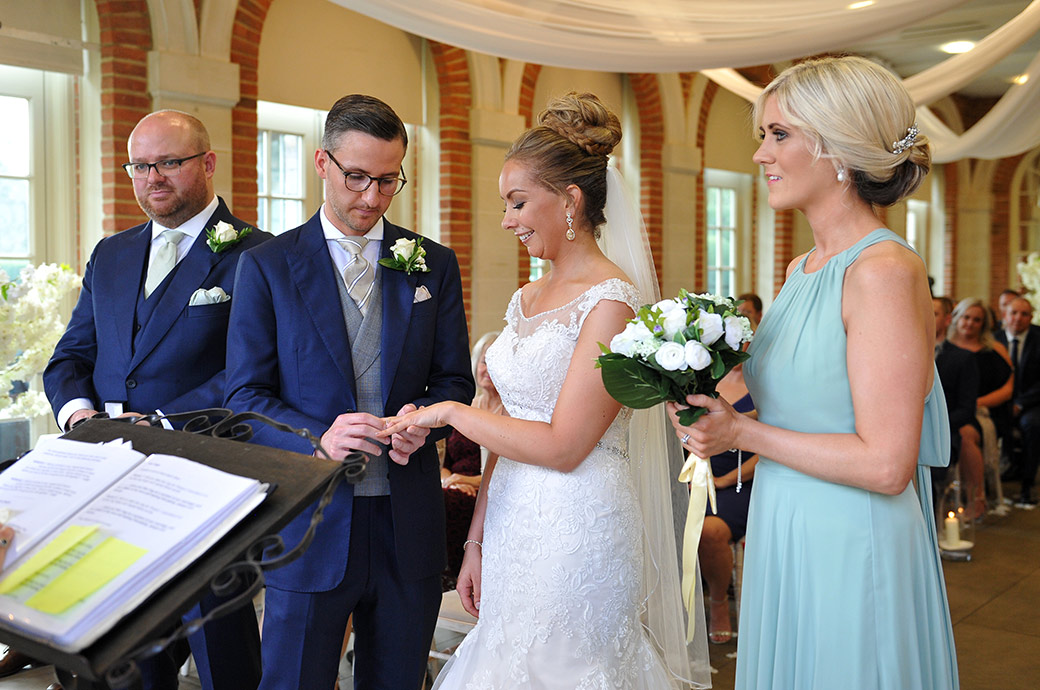 Groom captured in The Orangery at the wonderful Surrey venue Great Fosters in Egham carefully pushes the wedding ring onto his Bride's finger