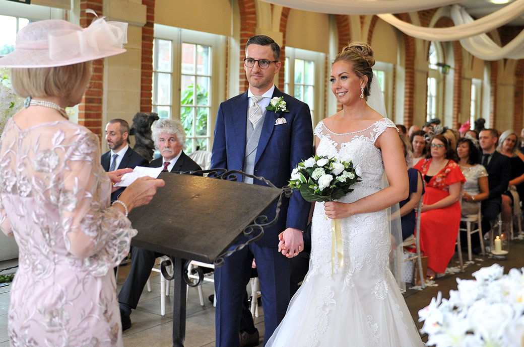 Bride and Groom watch and listen as a mother does a reading during the marriage ceremony in The Great Fosters Orangery Surrey wedding venue