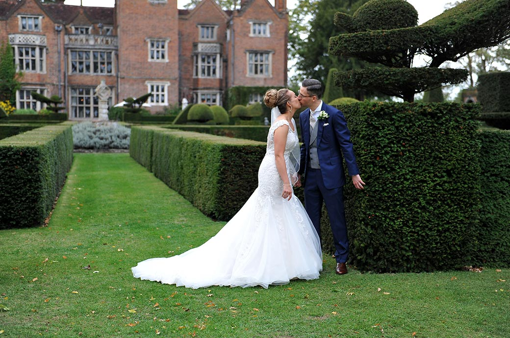 Lovely romantic wedding photograph of a handsome couple kissing during a walk in the beautiful grounds of the fabulous Great Fosters Surrey wedding venue in Egham village