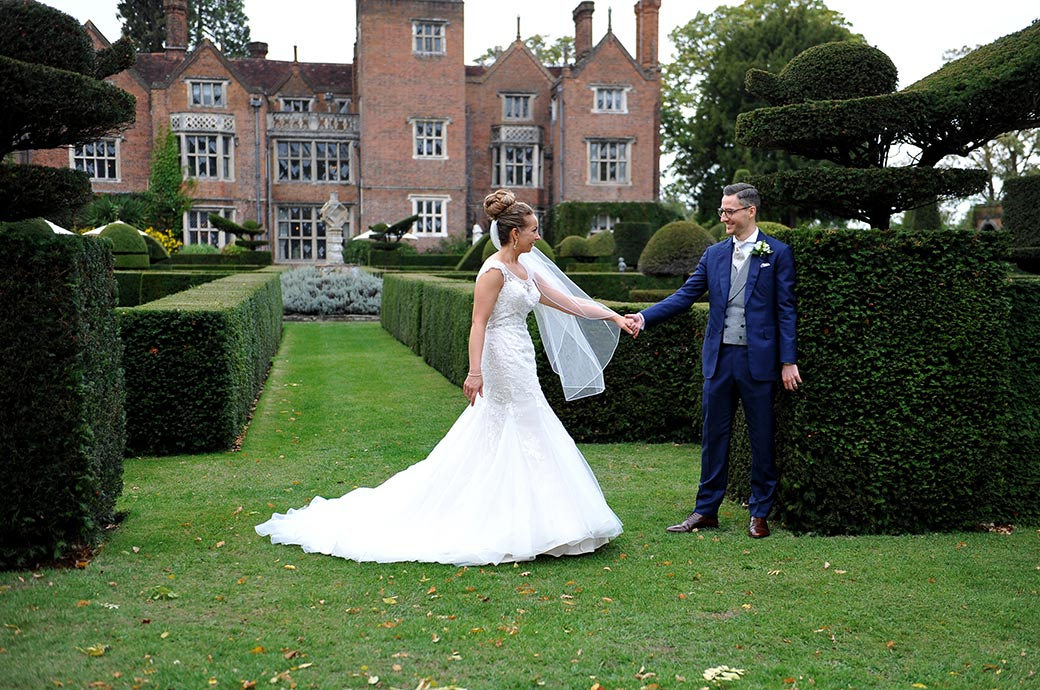 Truly romantic wedding picture of a Groom holding out his hand to bring his Bride to him captured in the beautiful grounds of Great Fosters in Egham Surrey
